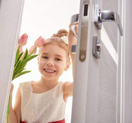 Dolce ragazza del bambino con il mazzo di tulipani. Bambina felice con il mazzo di fiori apre la porta. Matrimonio, concetto di San Valentino.