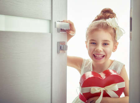 baby open present: Sweet child girl with red heart. Happy little girl with Valentines gift opens the door. Wedding, Valentine concept.