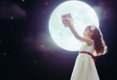 wedding guest: Sweet child girl with red heart. Happy little girl with gift box on background of the moon. Wedding, Valentine, celebration concept. Stock Photo
