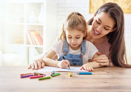 madre: Familia feliz. Madre e hija juntas pintan. Mujer adulta que ayuda a que el niño de la muchacha.