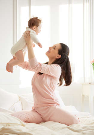 smiling mother: happy family. mother playing with her baby in the bedroom.