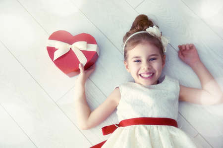 white heart: Sweet child girl with red heart. Happy little girl with Valentines gift on a white floor. Wedding, Valentine concept.