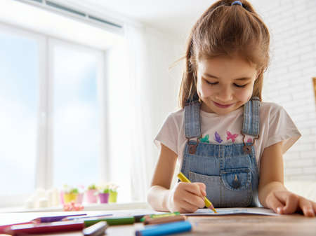 colored: Happy child plays. Little child girl draws with colored pencils. Stock Photo