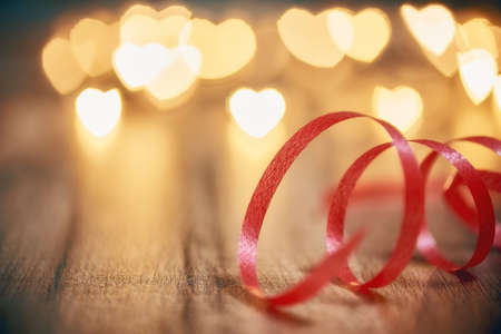 Garland lights on wooden rustic background. Valentines day background with red ribbon and hearts. The concept of love and Valentines day.