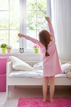 arms up: A nice child girl enjoys sunny morning. Good morning at home. Child girl wakes up from sleep.