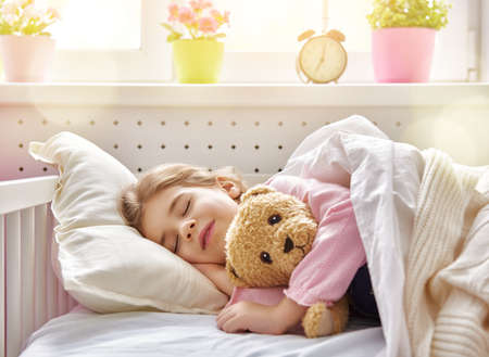 chicas sonriendo: Niña adorable niño durmiendo en la cama con su juguete. La niña abraza el oso de peluche.