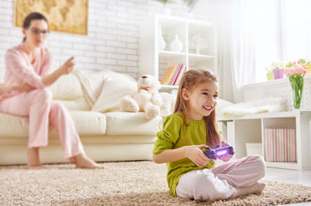 mum and child: happy child girl playing video games. mother frustrating that her child playing video games Stock Photo