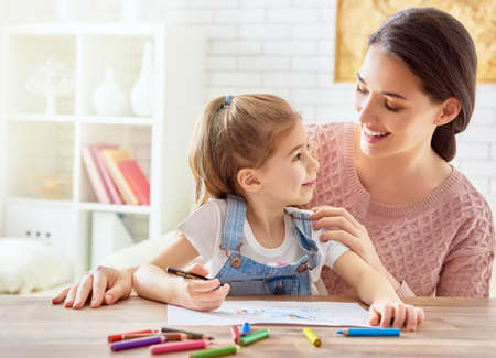 play of color: Happy family. Mother and daughter together paint. Adult woman helps the child girl.
