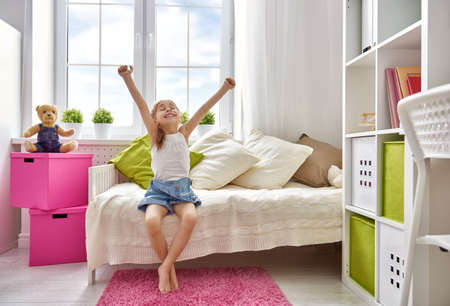 interior bedroom: A nice child girl enjoys sunny morning. Good morning at home. Child girl wakes up from sleep.