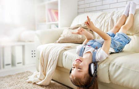 zábava: holčička se sluchátky doma. dítě dívka, poslech hudby.