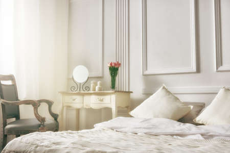 comfort room: bedroom in soft light colors. big comfortable double bed in elegant classic bedroom Stock Photo