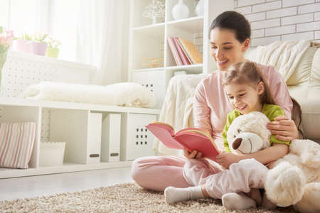 生活方式: 年輕漂亮的媽媽讀一本書給她的女兒