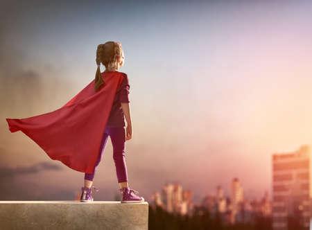 sen: Malé dítě dívka hraje superhrdinu. Dítě na pozadí západu slunce na obloze. Výkon koncept Girl