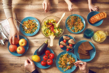 familia cenando: Vista superior de la cena con la familia juntos sentados en la mesa de madera rústica. Disfruta de una cena de la familia juntos.