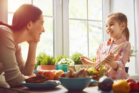 家族: 素朴な木製のテーブルに一緒に座って夕食を食べて幸せな家族。母と娘が一緒に家族の夕食を楽しみます。