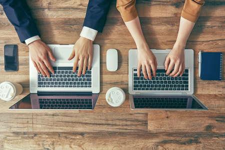 남자와 여자는 자신의 컴퓨터에서 작동합니다. 상단에서 볼 수 있습니다. 두 개의 노트북, 두 사람. 스톡 콘텐츠