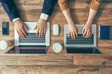 two on top: man and woman working on their computers. the view from the top. two laptops, two persons. Stock Photo