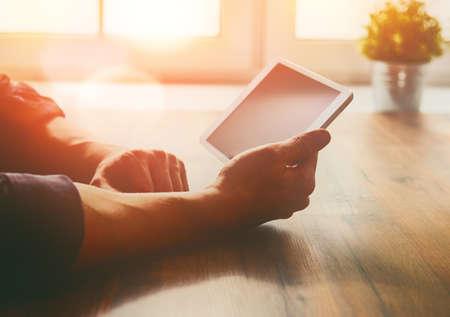 Persona del sexo masculino pensativo mirando a la pantalla de la tableta digital mientras está sentado en la mesa.