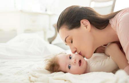 bebês: família feliz. mãe brincando com seu bebê no quarto.
