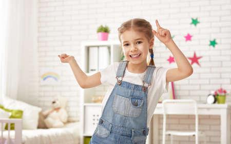 lustig Kind Mädchen spielt zu Hause. Mädchen, die Spaß und Tanz. Erholung und Unterhaltung zu Hause.