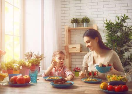 Cena de familia feliz juntos sentados en la mesa de madera rústica. La madre y su hija disfrutando de la cena de la familia juntos.