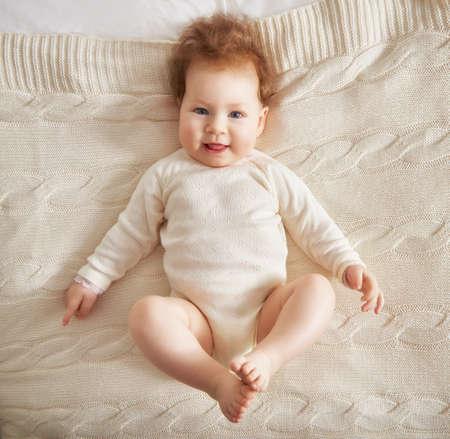 bebes lindos: Hermoso bebé sonriente lindo en la cama en la habitación. Niño feliz riendo.