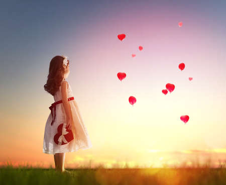 woman dress: Sweet child girl looking at red balloons. Balloons in shape of heart flying in the sunset sky. Wedding, Valentine, love concept.