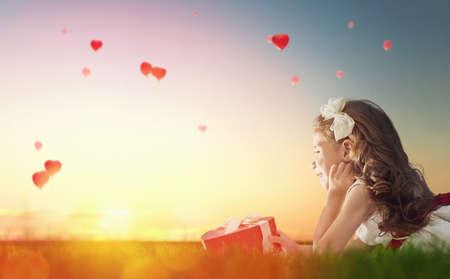 航空ショー: 赤い風船を見て甘い子女の子。夕焼けの空を飛んでいるハートの形の風船。結婚式、バレンタイン、愛の概念。