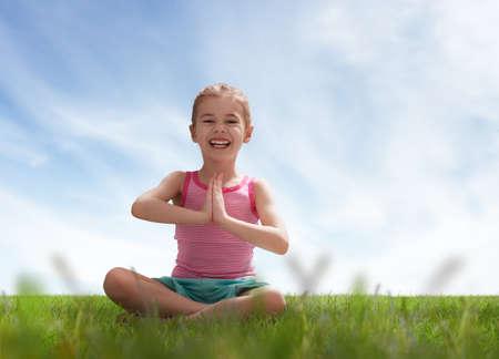 Kind praktizieren Yoga auf dem Rasen im Freien Standard-Bild
