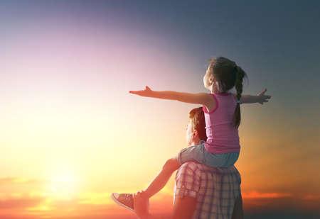 persona feliz: familia feliz en la puesta del sol. padre e hija que se divierte y que juega en la naturaleza. el niño se sienta en los hombros de su padre.