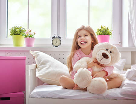 wake: The child girl woke up and enjoys the morning sun. Girl laugh and hugs the teddy bear.