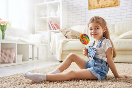posing: funny child girl plays at home. girl eating candy and resting. recreation and entertainment at home.