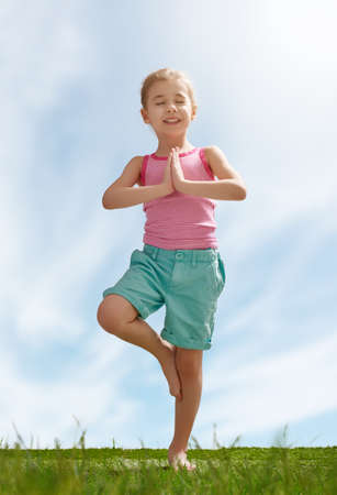 family exercise: child practicing yoga on the grass outdoors