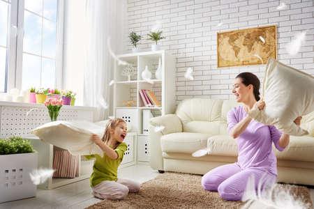 家族: 幸せな家族!母と彼女の子供の女の子が枕を戦っています。幸せな家族のゲーム。
