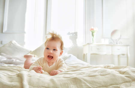baby bed: Beautiful smiling cute baby girl on the bed in the room. Happy child laughing.