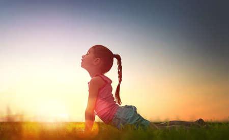 公園で子供の女の子。公園での夕暮れヨガ。女の子は、ヨガを練習しています。