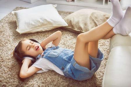 escucha activa: niña con auriculares en casa. Chica niño escuchando música.