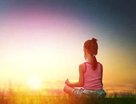 zen attitude: fille de l'enfant dans le parc. Yoga au coucher du soleil dans le parc. Fille pratique le yoga.