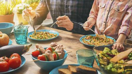 Rodzina posiadające kolację razem siedzi na drewnianych tabeli. Korzystających ze sobą rodzinny obiad.
