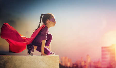 child: Little child girl plays superhero. Child on the background of sunset sky. Girl power concept