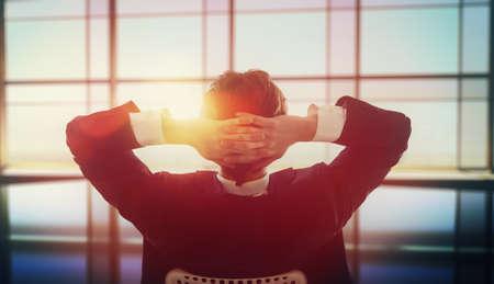 生活方式: 滿意所做的工作。快樂的年輕商人望著在辦公室的窗戶。