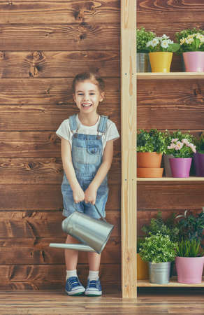 flowers garden: Cute child girl caring for her plants. Girl watering flowers in pots. Spring concept, nature and care. Stock Photo