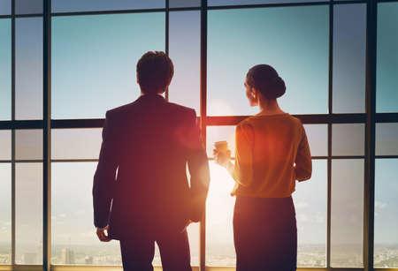 成功したビジネス人々 のチーム。安静時、事務所で話している 2 人のビジネスマン。男と女は、ビジネス センターの窓から街を見てください。 写真素材
