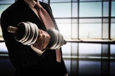 fortaleza: exitoso hombre de negocios con una mancuerna pesada. el concepto de éxito en un trabajo duro de negocio.