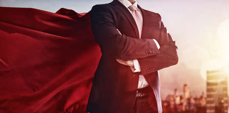 freedom: superhero businessman looking at city skyline at sunset. the concept of success, leadership and victory in business. Stock Photo