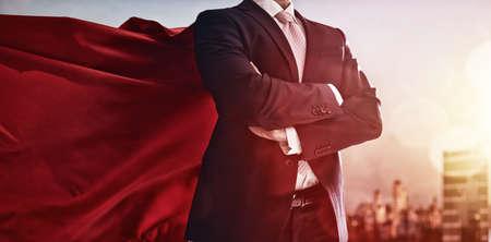 koncept: superhjälte affärsman tittar på stadens silhuett på solnedgången. begreppet framgång, ledarskap och seger i näringslivet. Stockfoto