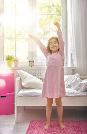 Una buena chica niño disfruta mañana de sol. Buenos días en casa. La muchacha del niño se despierta de su sueño.
