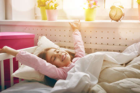 early childhood: A nice child girl enjoys sunny morning. Good morning at home. Child girl wakes up from sleep.