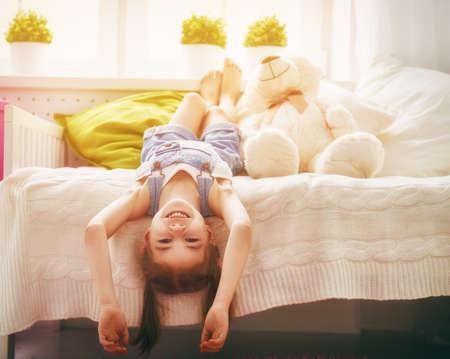 menina engraçada joga em casa. menina se divertindo e descansando. recreação e entretenimento em casa.