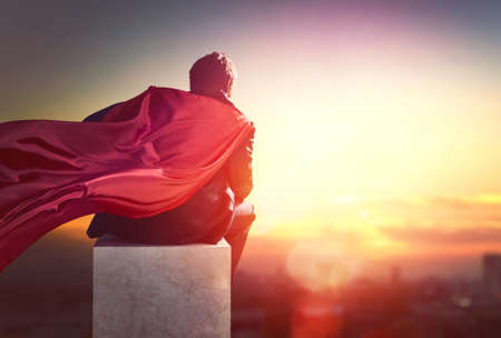 gente exitosa: superhéroe empresario mirando la silueta de la ciudad al atardecer. el concepto de éxito, el liderazgo y la victoria en los negocios.